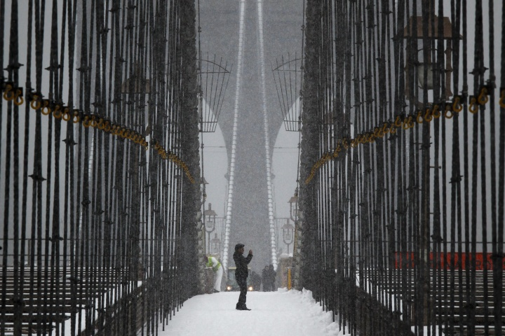A man takes pictures from the Brooklyn Bridge during a snowstorm in New York March 8, 2013. — Reuters Photo