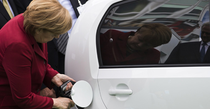 German Chancellor Angela Merkel plugs a charging nozzle into an electric car at the Electric Mobility Conference of the German government in Berlin May 27, 2013.  — Reuters Photo