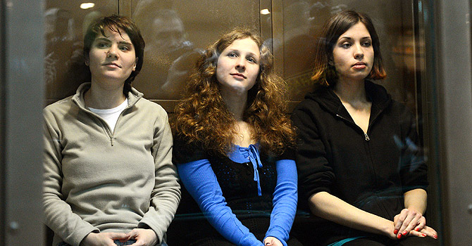 "Members of the all-girl punk band ""Pussy Riot"" (from L) Maria Alyokhina, Yekaterina Samutsevich and Nadezhda Tolokonnikova sitting in a glass-walled cage in Moscow, on October 10, 2012 . A Moscow court heard today the appeal of feminist punks Pussy Riot against their two-year prison camp sentence, days after President Vladimir Putin appeared to give his blessing to the verdict. — AFP Photo"