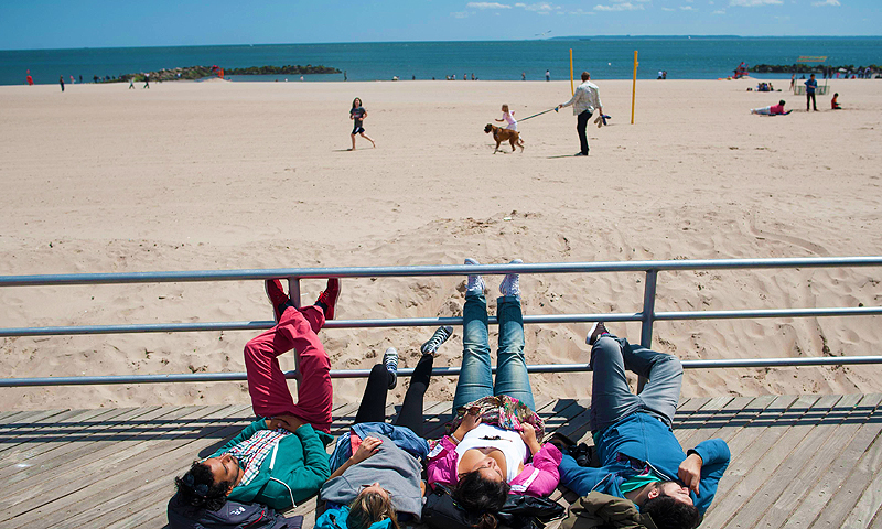 People lay along the boardwalk in Coney Island in the Brooklyn Borough of New York, May 26, 2013. Seven months after Hurricane Sandy, New York's beaches have reopened ahead of the Memorial Day holiday. — Reuters Photo
