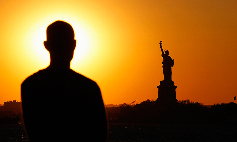A man looks out at the Statue of Liberty as the sun sets in New York, May 26, 2013. The statue and Liberty Island will reopen to the public on July 4 after having been damaged by Hurricane Sandy last year. — Reuters Photo