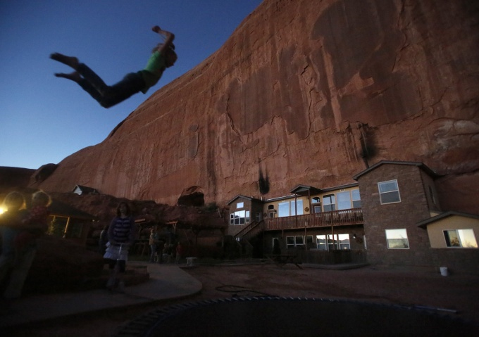 "Girls play on a trampoline near a home blasted from a rock wall at the Rockland Ranch community outside Moab, Utah, November 2, 2012. The ""Rock"" as it is referred to by the approximately 100 people living there in about 15 families, was founded about 35 years ago on a sandstone formation near Canyonlands National Park. Polygamy was a part of the teachings of The Church of Jesus Christ of Latter-day Saints and was brought to Utah by faithful Mormons in the late 1840s."