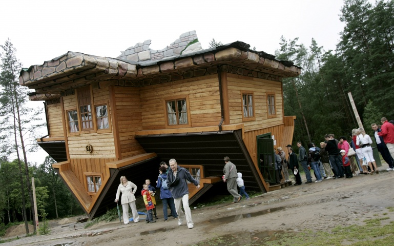 People wait in line to visit an upside-down house built at the Centre of Education and Promotion of the Region in the village of Szymbark, northern Poland July 31, 2007. The upside-down house created by Daniel Czapiewski is supposed to describe the times of the former communist era and the present times in which we live.