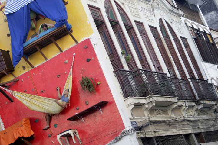"Brazilian artists Tiago Primo (top) and his brother Gabriel hang out at a wall in Rio de Janeiro July 8, 2009. The bizarre vertical ""house"" built on a climbing wall by Brazilian artists has been drawing the attention of thousands who walk by the installation in Rio de Janeiro's downtown neighbourhood."