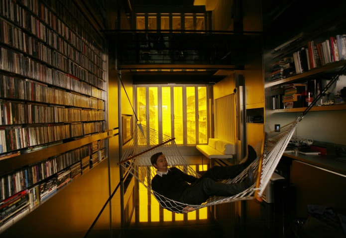 "Hong Kong architect Gary Chang rests in a hammock inside his 32-square-metre apartment in Hong Kong January 28, 2010. After three decades in the same boxy dwelling Chang grew up in, he has come up with an innovative answer to the increasingly cramped lives of many urban dwellers -- the science fiction-like ""domestic transformer"". Picture taken January 28, 2010."