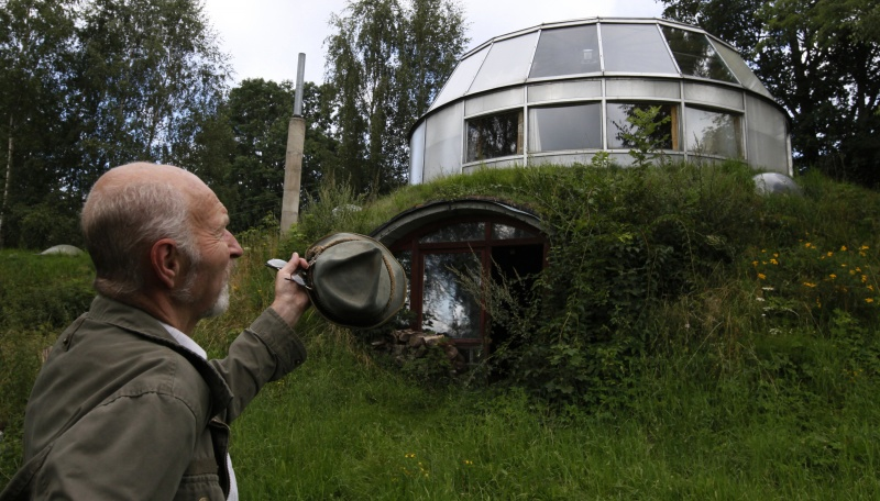 Bohumil Lhota, a 73-year-old builder, stands in front of the house which he built in Velke Hamry, near the town of Jablonec nad Nisou, 100km (62 miles) north-east from Prague, August 7, 2012. Lhota conceptualized the idea to create the unique house and started to build it in 1981, building it close to nature to benefit from the cooler ground temperature. Lhota's house, which is built in 2002, is able to move up and down and rotate on its sides, which allows him to adjust to his preferred window view.