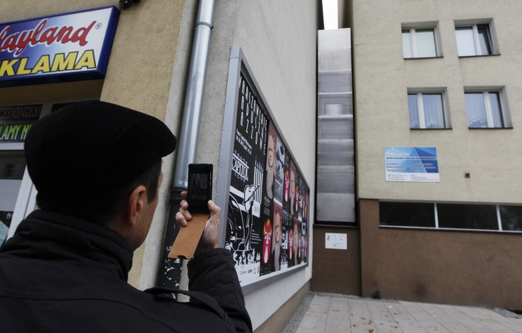 A man takes a picture of the one of the world's narrowest buildings, built as an artistic installation wedged between two existing buildings, in Warsaw October 23, 2012. A building just 92 cm (36 inches) wide as its narrowest point was opened in Warsaw on October 20 as an artistic installation that will be a home from home for Israeli writer Edgar Keret. Keret, who told news channel TVN24 he would live there when he visits Warsaw twice a year, said he conceived the project as a kind of memorial to his parents' fami
