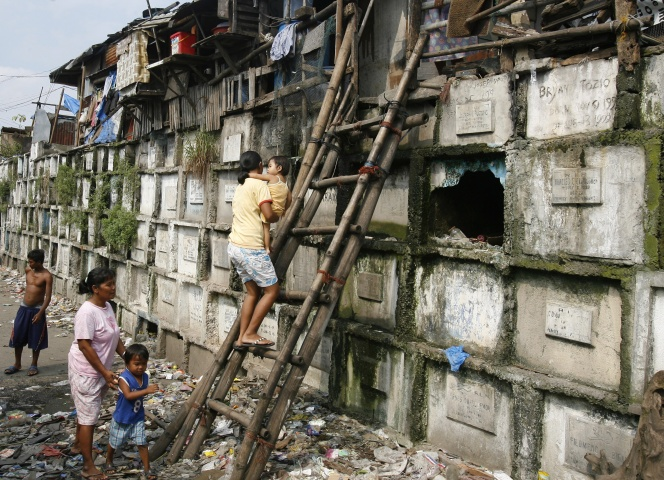 Residents climb into their houses atop gravestones inside a cemetery in Manila October 21, 2008. Many poor urban dwellers make their homes in public cemeteries, converting abandoned tombs and mausoleums into houses. The local government plan to move out the hundreds of people who live in the cemeteries around the city before the upcoming All Souls' Day, a day of remembrance for the dead when Catholics visit the graves of their relatives.