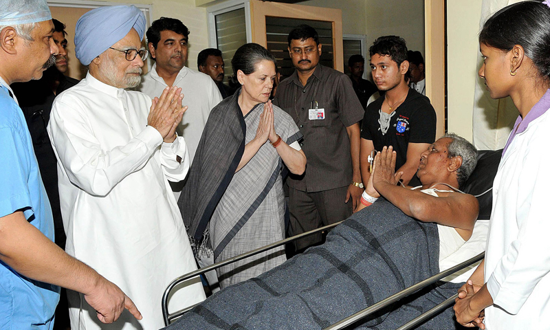 In this handout photograph received from the Press Information Bureau (PIB) on May 26, 2013 Indian Prime Minister Manmohan Singh (2L) and chairperson of the National Advisory Council, Sonia Gandhi (4L) meet an injured person at the Rama Krishna Care Hospital in Raipur, capital of central Chhattisgarh state.— AFP PHOTO