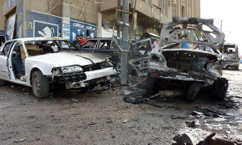 Destroyed cars sit at the site of a blast in Baghdad on May 30, 2013. — Photo by AFP