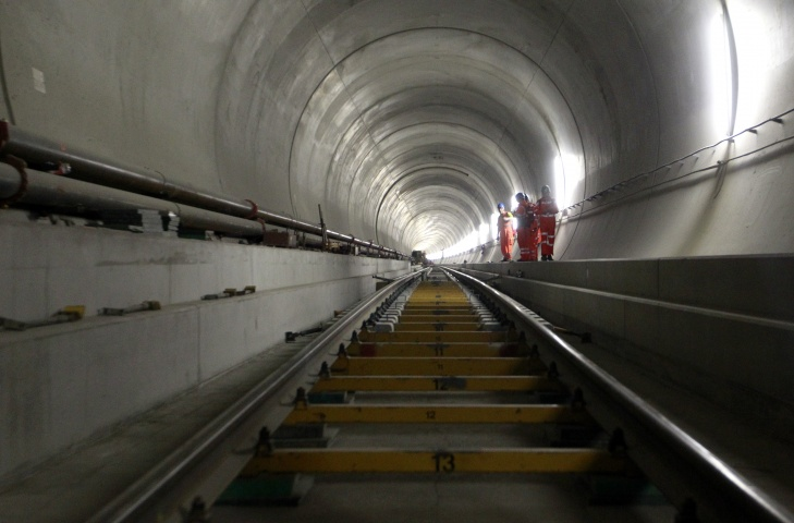 Journalists stand beside rail tracks at the construction site in the Neat Gotthard Base tunnel near Sedrun April 2, 2013.