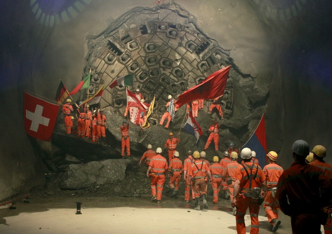 Miners wave with the flags of their home countries as they celebrate after a giant drill machine broke through the rock at the final section Sedrun-Faido.