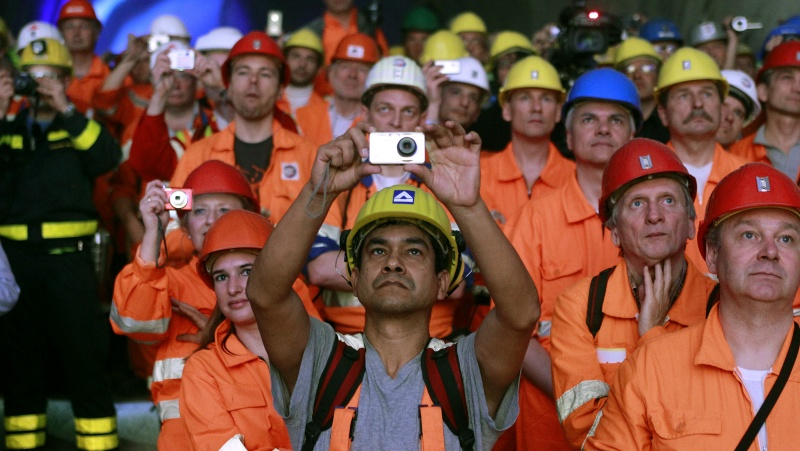 Miners and visitors take pictures as a giant drill machine breaks through the rock at the western tunnel section Sedrun-Faido.