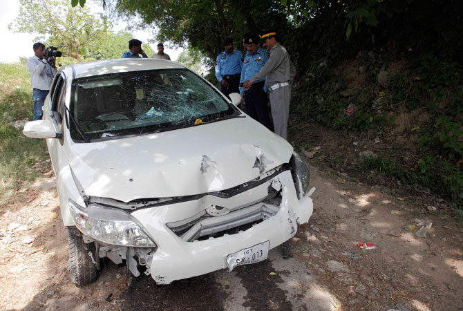 Security officials inspect the damaged car, which Zulfikar was travelling in, when he came under attack by unidentified gunmen, in Islamabad May 3, 2013. — Reuters Photo