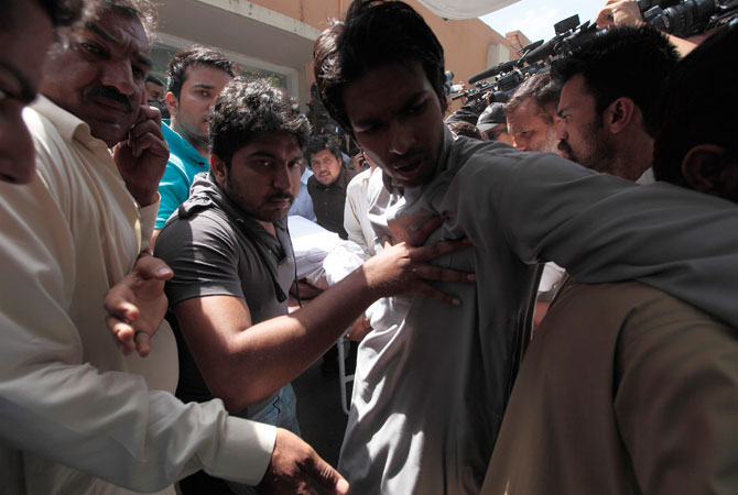 Qamar Abbas (C), son of prosecutor Chaudhry Zulfikar, pushes onlookers out of the way as his father's body is loaded into an ambulance. — Reuters Photo