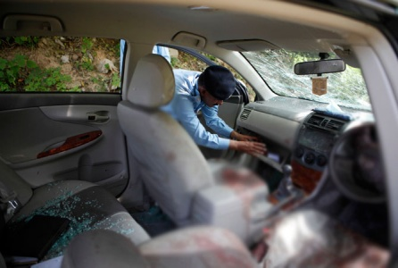 A policeman collects evidence from Chaudhry Zulfiqar's car. — Reuters Photo