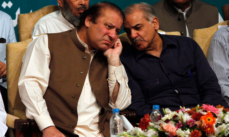 Nawaz Sharif (L), incoming prime minister and leader of PML-N, talks with his brother Shahbaz Sharif before addressing his party members who were voted to political posts in the general election, during a function in Lahore, May 20, 2013. — Photo by Reuters