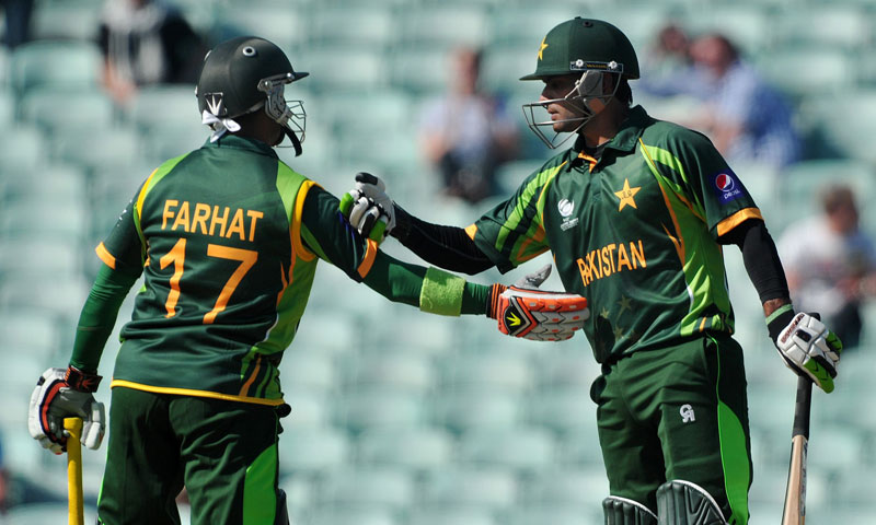 Pakistan's Imran Farhat (L) congratulates teammate Mohammad Hafeez on his half century — AFP Photo