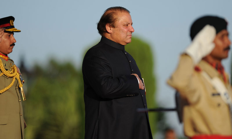 Nawaz Sharif (C) observes the national anthem during a welcoming ceremony at the Prime Minister House in Islamabad on June 5, 2013. — AFP Photo