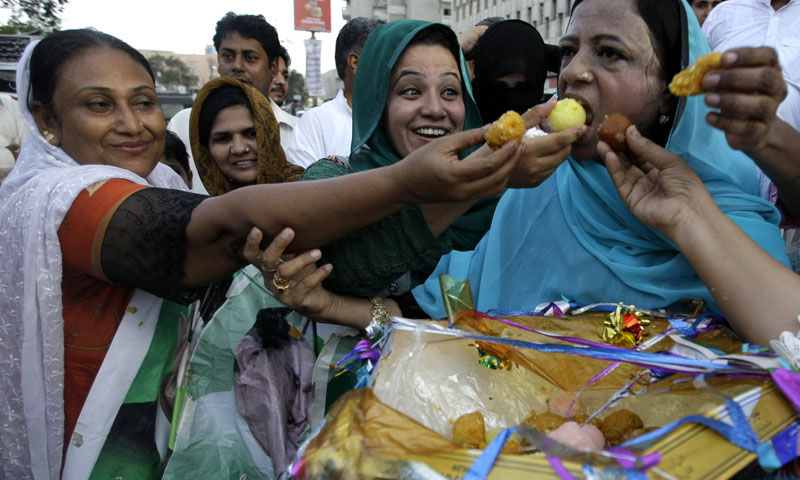 Supporters of Pakistan's newly elected Prime  Minister Nawaz Sharif exchange sweets to celebrate in Karachi, Pakistan on Wednesday, June 5, 2013. — AP Photo