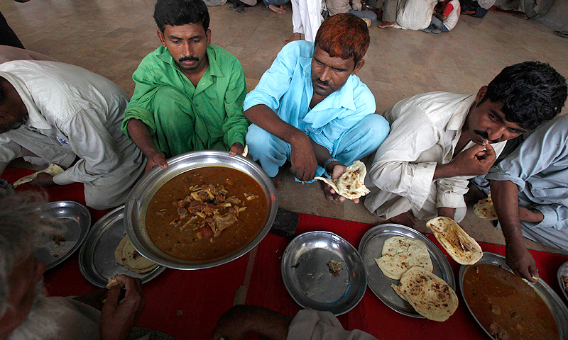Men eat at the Saylani Welfare Trust food distribution centre in Karachi, June 5, 2013.