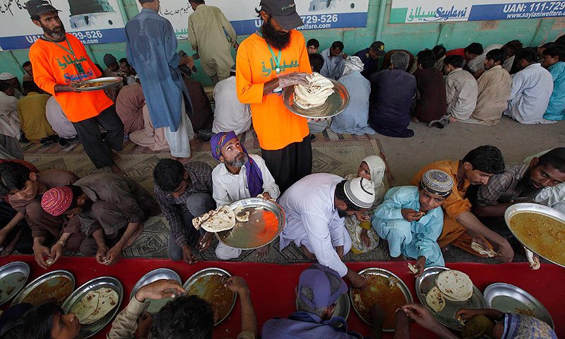 Volunteers serve food to people at a Saylani Welfare Trust food distribution centre in Karachi, June 5, 2013.