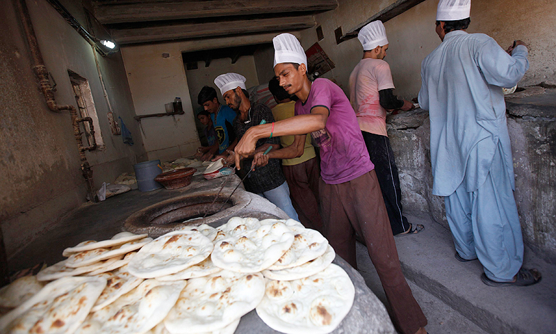 Workers prepare roti (flat bread) at the Saylani Welfare Trust's food distribution stalls in Karachi, June 5, 2013.
