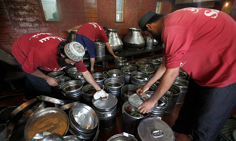 Workers place caps on pots filled with mutton curry, before their distribution, in the Saylani Welfare Trust office building in Karachi, June 5, 2013.