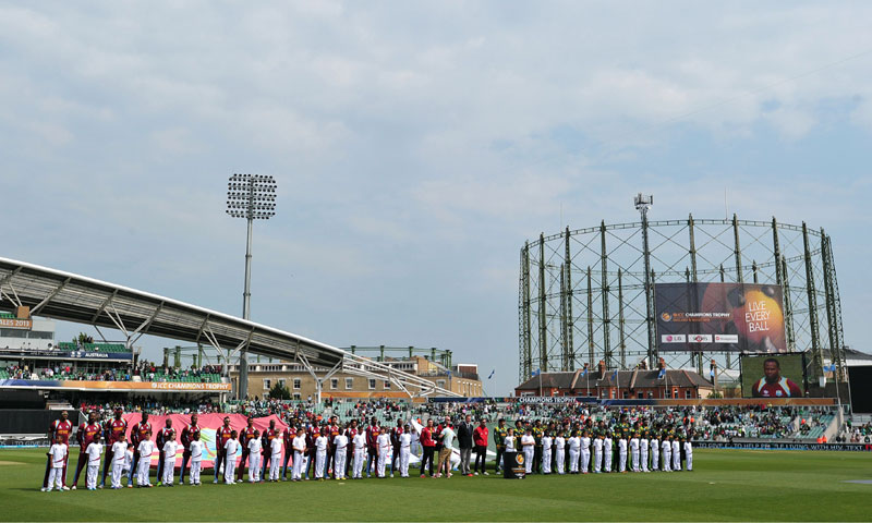 The teams line up for the national anthem ceremony. — AFP Photo