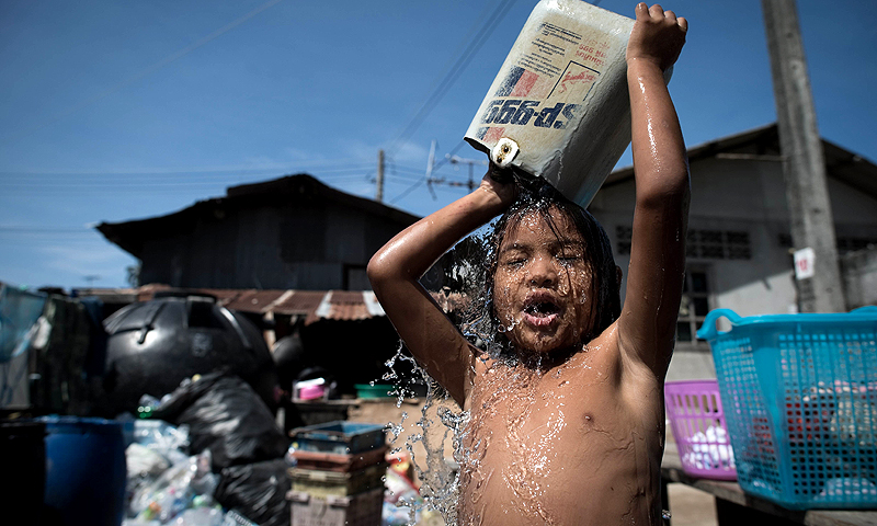 This picture taken on February 16, 2013 shows the daughter of a sea gypsy taking a shower on a street in Rawai, southern Thailand. The once-nomadic hunter-gatherers roamed the seas off the Andaman Coast for generations, but Thailand's sea gypsies say their traditional way of life is under threat and their homes at risk from a tourism boom.