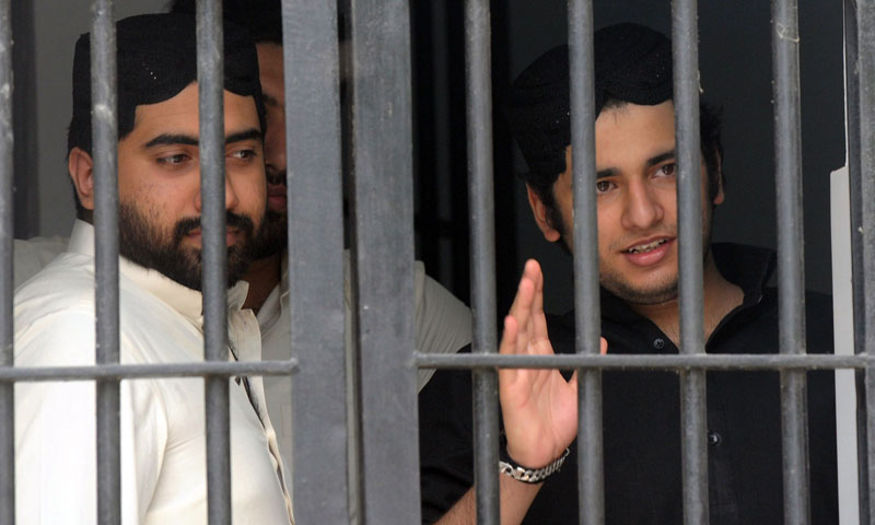 Shahrukh Jatoi (R) gestures while his accomplice Siraj Talpur looks on from a court lockup before being convicted for murder in the Karachi on June 7, 2013. —AFP Photo