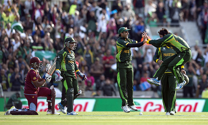 Saeed Ajmal (R) jumps to celebrate taking the wicket of West Indies' Dwayne Bravo. -Photo by AFP