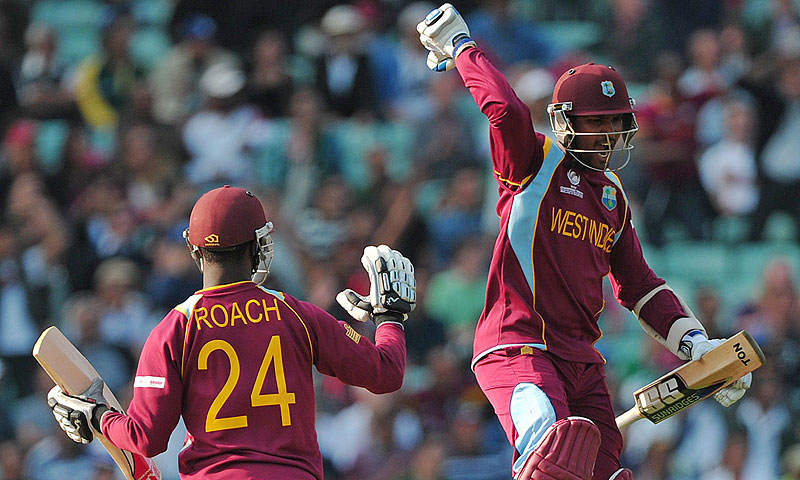 West Indies cricketer Denesh Ramdin (R) celebrates after team-mate Kemar Roach (L) hit a four to win. -Photo by AFP