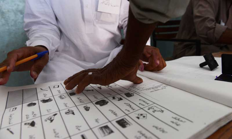 A resident marks a ballot book with his thumbprint before casting his vote at a polling station. — Photo by AFP