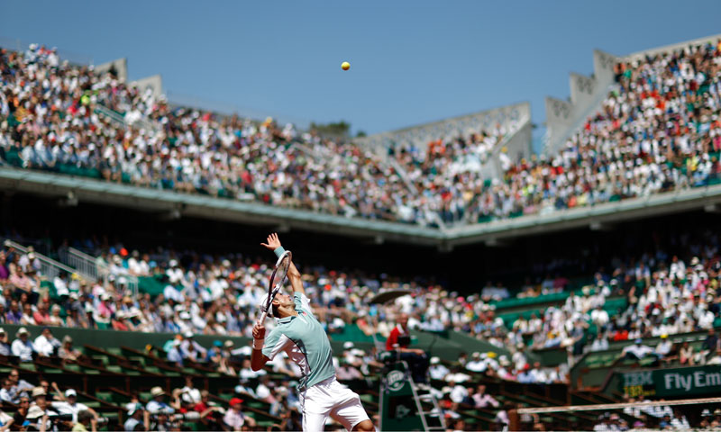 Novak Djokovic serves to Rafael Nadal. — AFP Photo