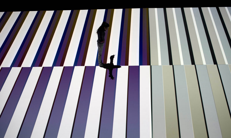 A visitor walks as a pattern is projected onto the floor during the world premiere of a new work by the Paris based Japanese artist Ryoji Ikeda in Sydney on June 7, 2013, as part of VIVID Sydney festival. — AFP Photo