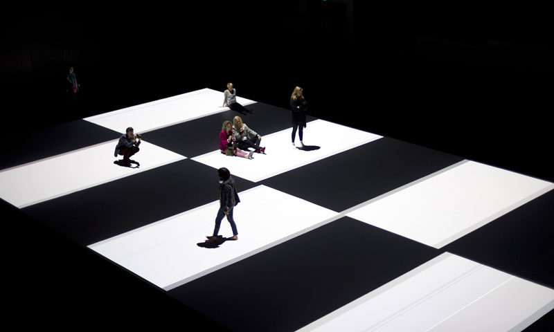 Visitors gather on a pattern that is projected onto the floor during the world premiere of a new work by the Paris based Japanese artist Ryoji Ikeda in Sydney. — AFP Photo