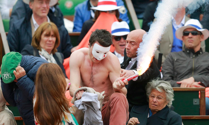 A flare-wielding Homen group protester tries to climb over a barrier onto the Philippe Chatrier clay court during the men's singles final match in Paris June 9, 2013. – Photo by Reuters