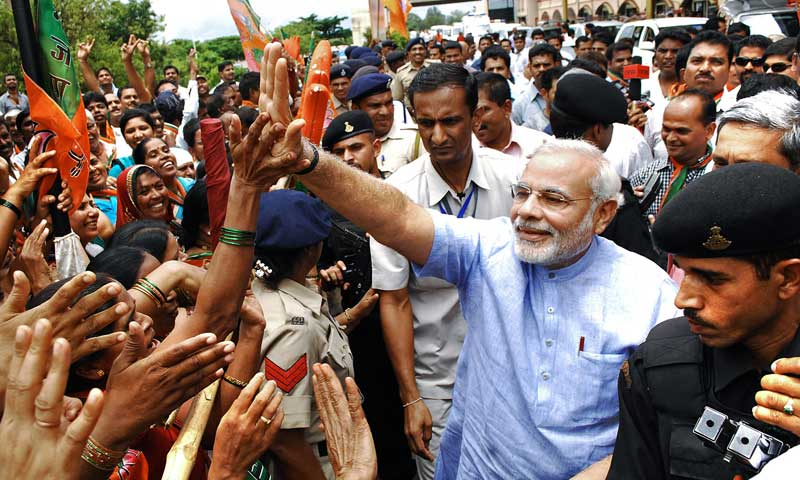 India's Gujarat state Chief Minister Narendra Modi greets supporters following his arrival at the Dabolim airport at Vasco in Goa, June 7, 2013. — Photo by AFP