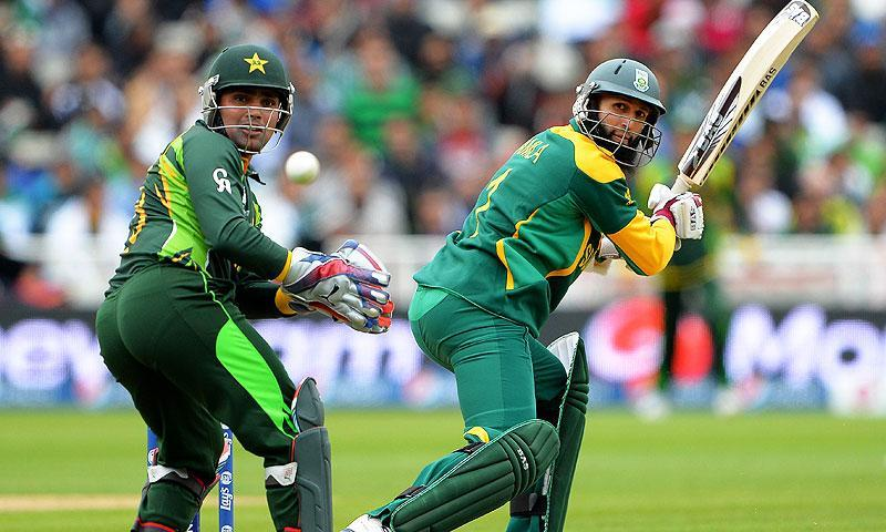 South Africa's Hashim Amla (R) scores runs past Pakistan's Kamran Akmal. -Photo by AFP