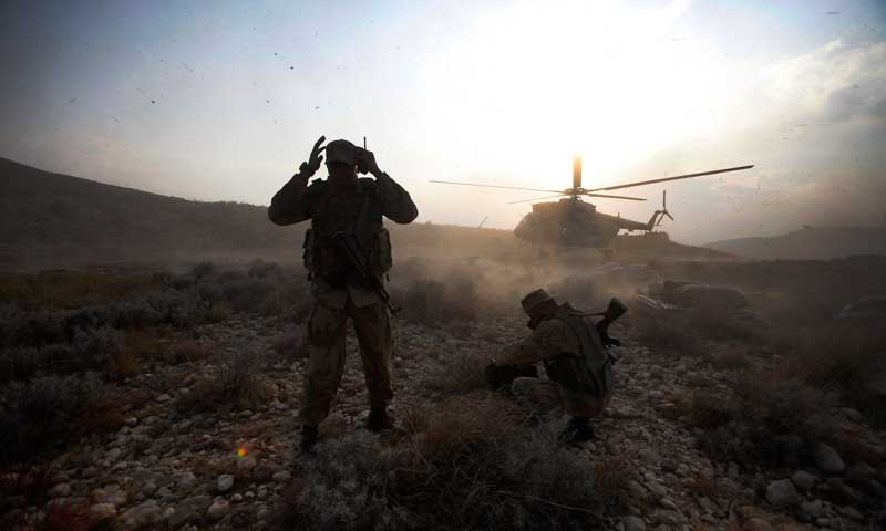 Soldiers crouch as a helicopter lands on top of Kund mountain near Kotkai village in South Waziristan, October 29, 2009. — Photo by Reuters/File