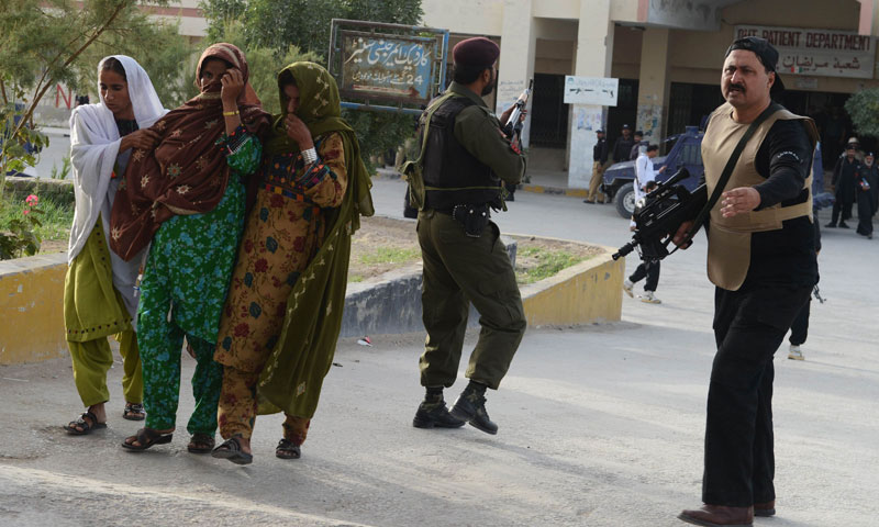 Women help a patient (2L) get away during a paramilitary operation against militants at the Bolan Medical Complex in Quetta, the capital of Balochistan province, on June 15, 2013.—AFP Photo