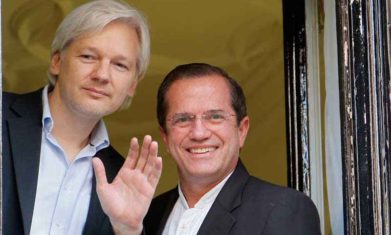 WikiLeaks founder Julian Assange waves from a window with Ecuador's Foreign Affairs Minister Ricardo Patino (R) at Ecuador's embassy in central London, June 16, 2013. Assange sought asylum in the embassy on June 19, 2012, in an attempt to avoid extradition to Sweden. — Photo by Reuters