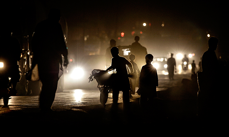 Silhouetted against vehicle's headlights, people walk on a street darkened by power cuts on the outskirts of Islamabad.