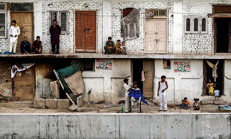 During a power cut Pakistanis gather outside to escape the heat trapped in their homes while a street barber gives a customer a haircut in Rawalpindi, Pakistan.