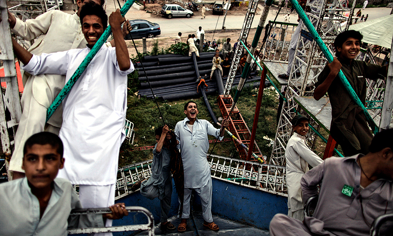 Pakistani youths enjoy a ride at a makeshift entertainment park set up outside a shrine in Rawalpindi, Pakistan.