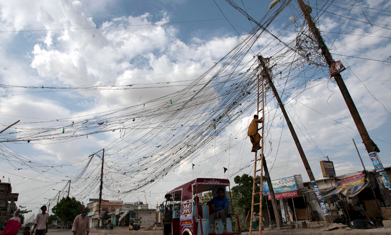 A resident climbs on a pole to adjust an illegal power connection from the transmission line on the outskirts of Karachi.
