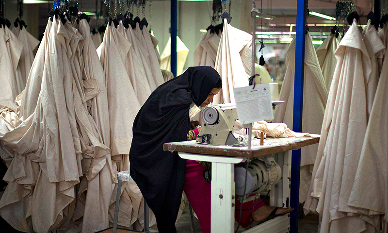 A worker uses a sewing machine at a textile factory that is partially run by privately-produced power in Faisalabad.
