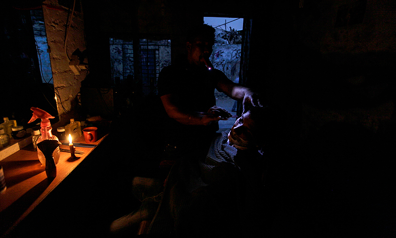 A barber shaves a customer's beard by the light of a candle and a mobile phone, during a power outage in Islamabad.