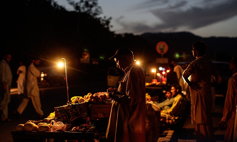 Fruit and food vendors use gas lamps to light their carts while waiting for customers outside a hospital on a dark roadside in Islamabad.